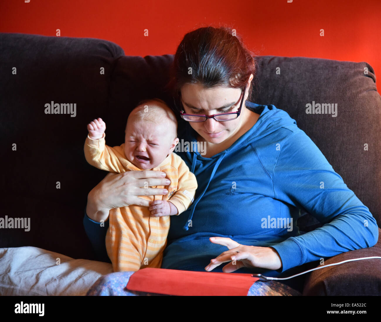 a-mother-in-pyjamas-using-an-ipad-and-ignoring-her-crying-baby-EA522C.jpg