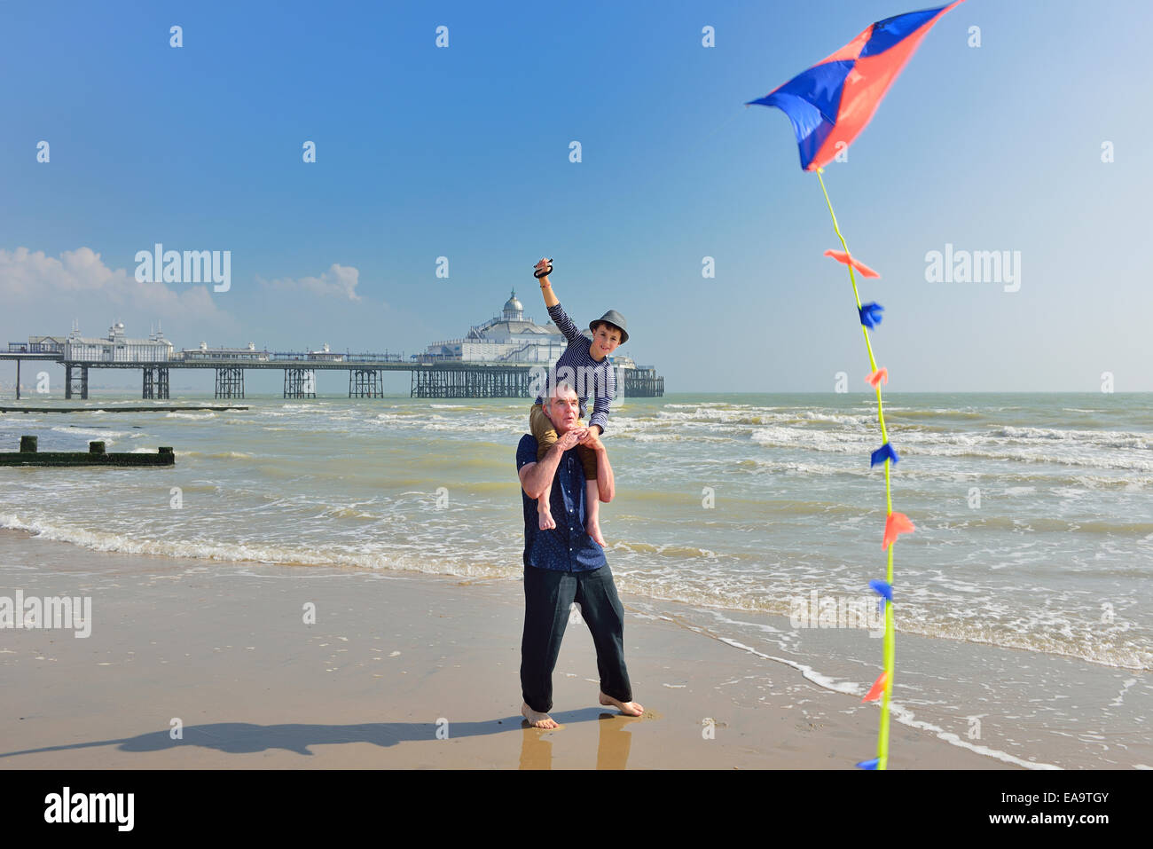 Grandfather with grandson flying a kite on the beach at Eastbourne. East Sussex. UK Stock Foto