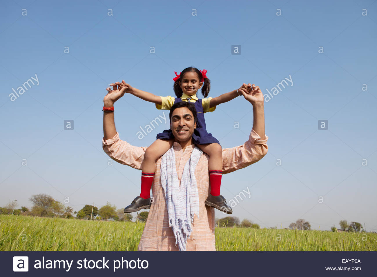 Indian man carrying his daughter on his shoulders Stock Foto