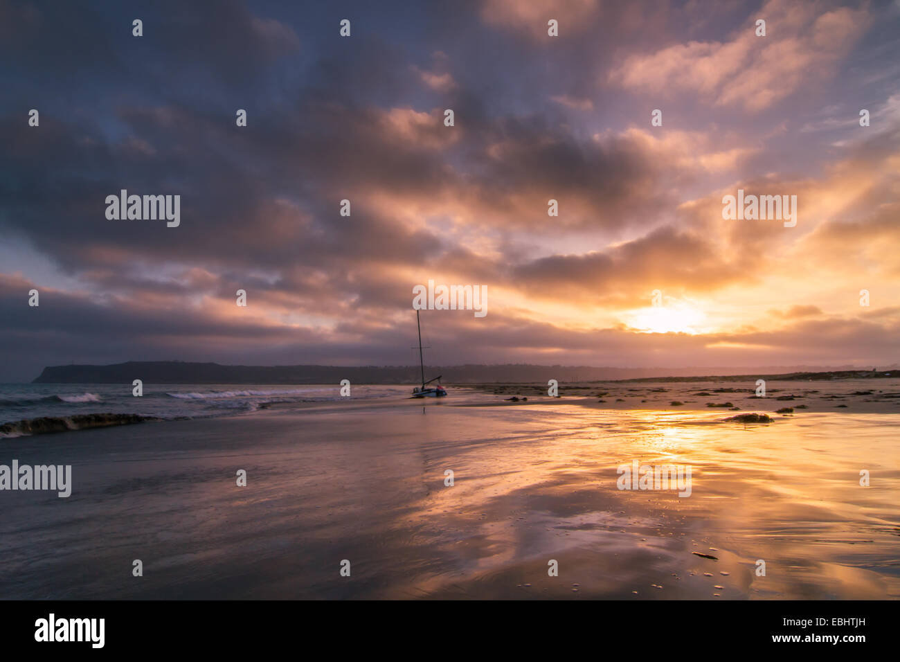 A stunning sunset over a sailboat reflected in the surf of Coronado Island near San Diego, California Stock Photo