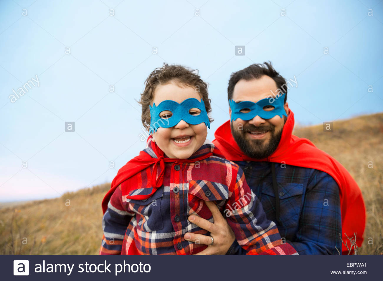 Portrait of father and son in superhero capes Stock Foto