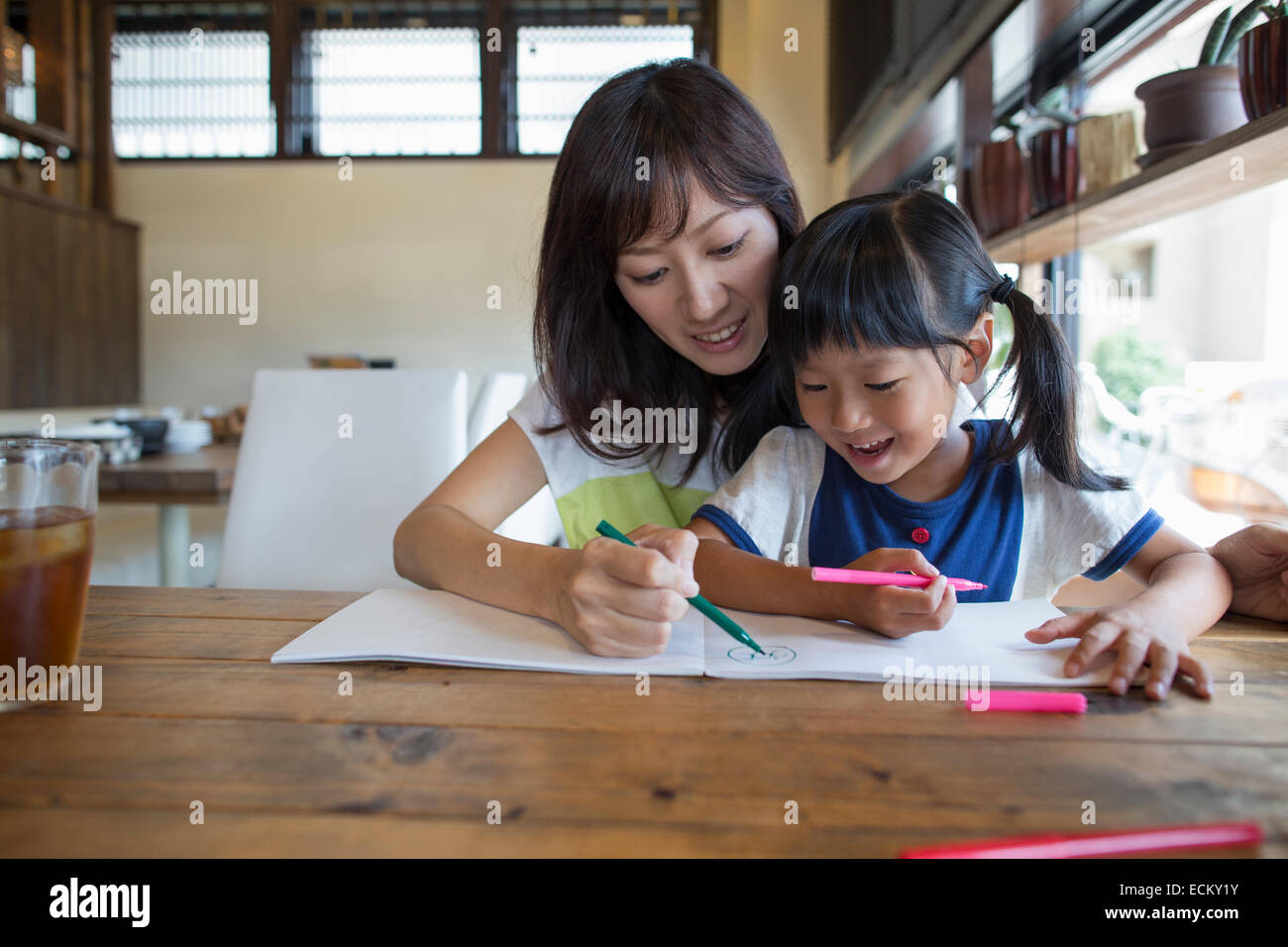 Mother and daughter sitting at a table, drawing with felt tip pens, smiling. Stock Foto
