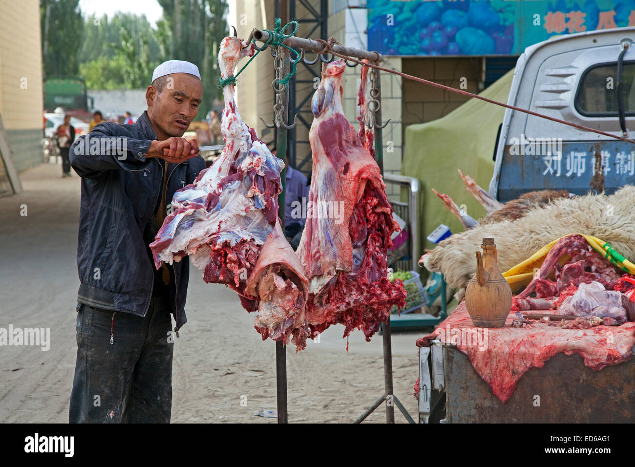 Butcher cutting meat from his pickup truck in the village Waxxari, oasis town in the Taklamakan Desert, Xinjiang Stock Photo