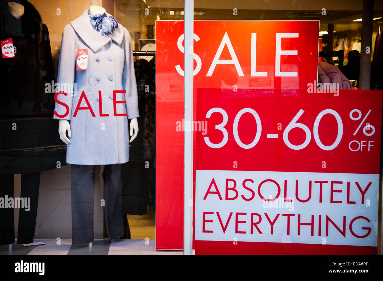 large sale sign posters in a shop window showing clothes