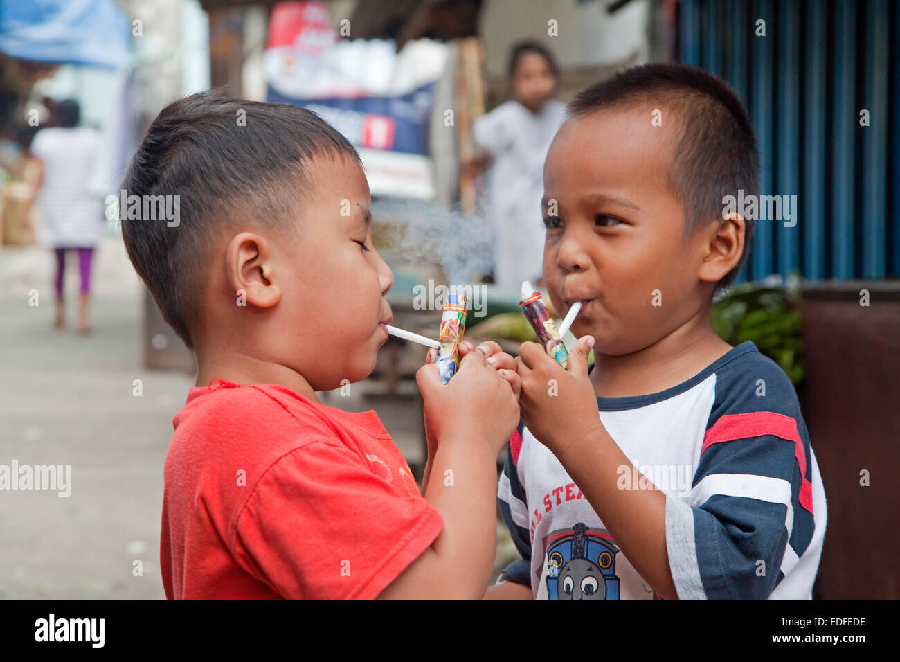 Indonesian children being taught how to smoke by being allowed to puff away on home-made pipes called Popeye Lauts, Stock Photo