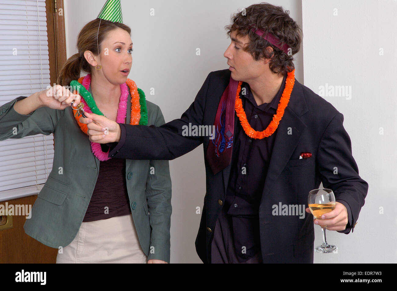 A woman at an office party taking car keys away from a disheveled looking man who has been drinking alcohol. Stock Photo