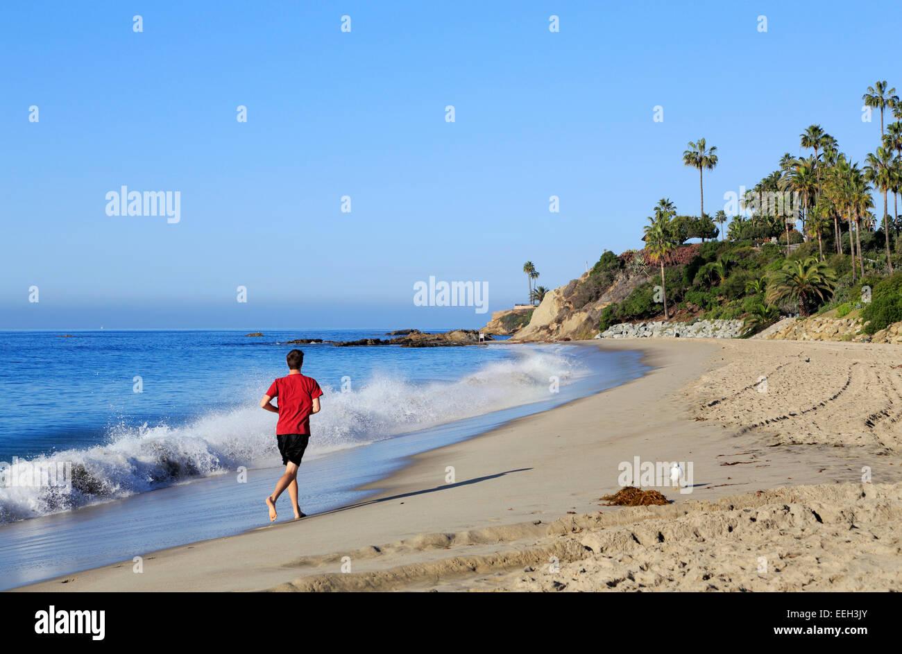 laguna-beach-orange-county-california-man-running-on-the-beach-EEH3JY.jpg