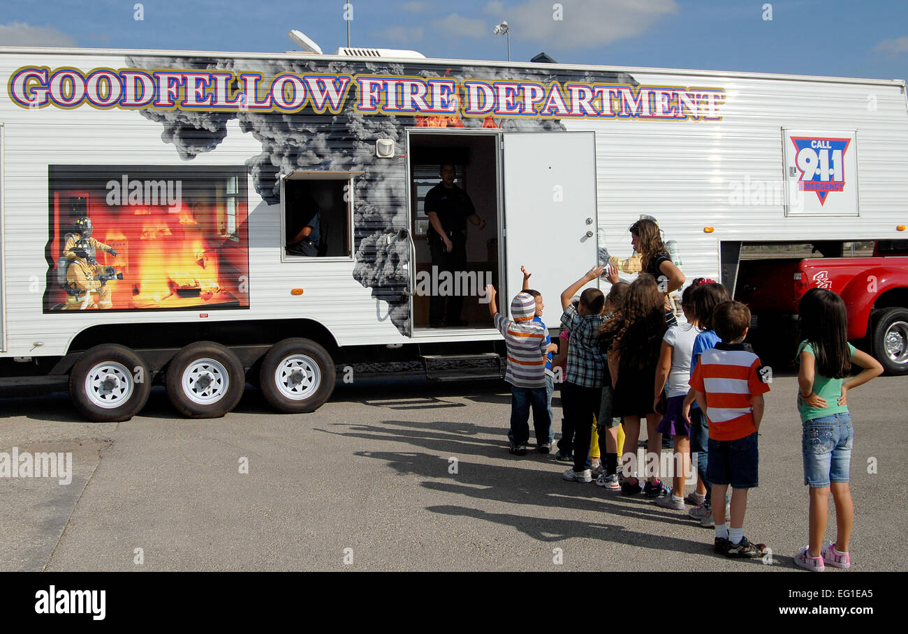 Children line up to enter a fire safety house outside the for Fire safety house