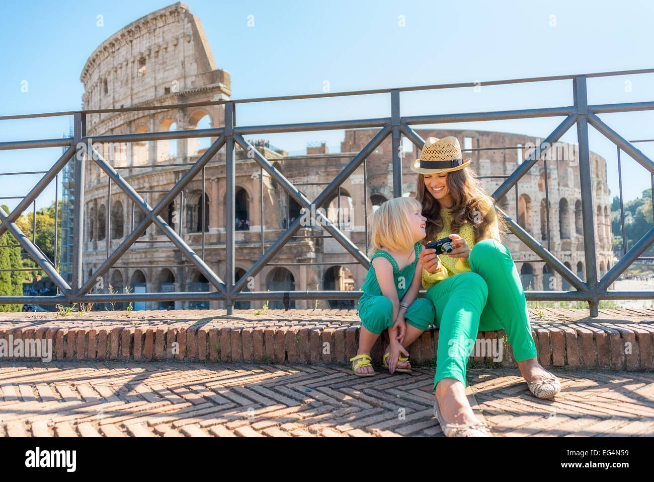 Mother and baby girl sitting in front of colosseum in rome, italy Stock Foto
