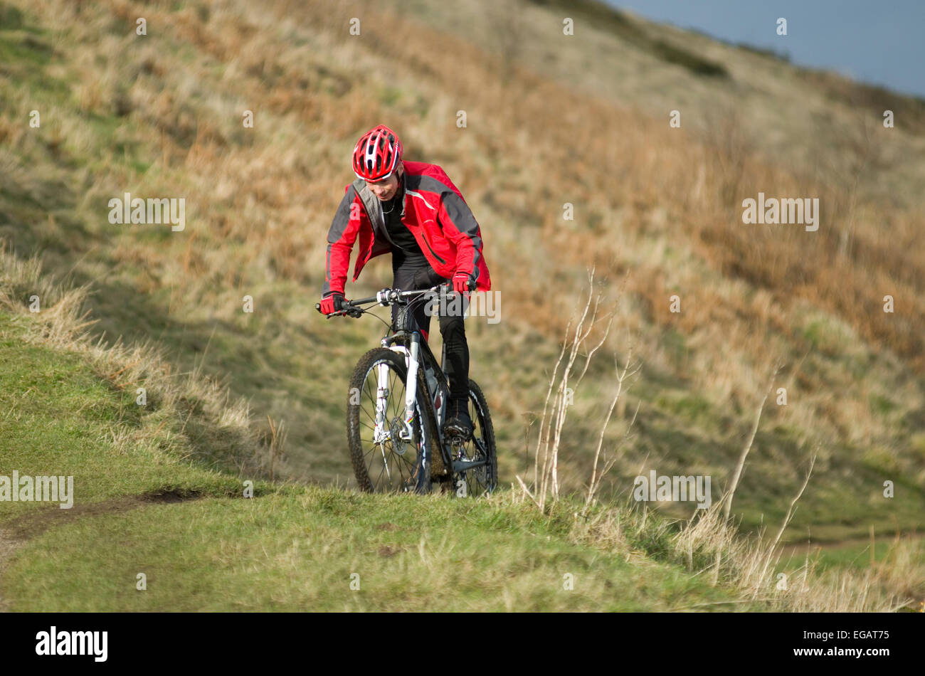 mountain-biker-in-red-coat-and-helmet-on