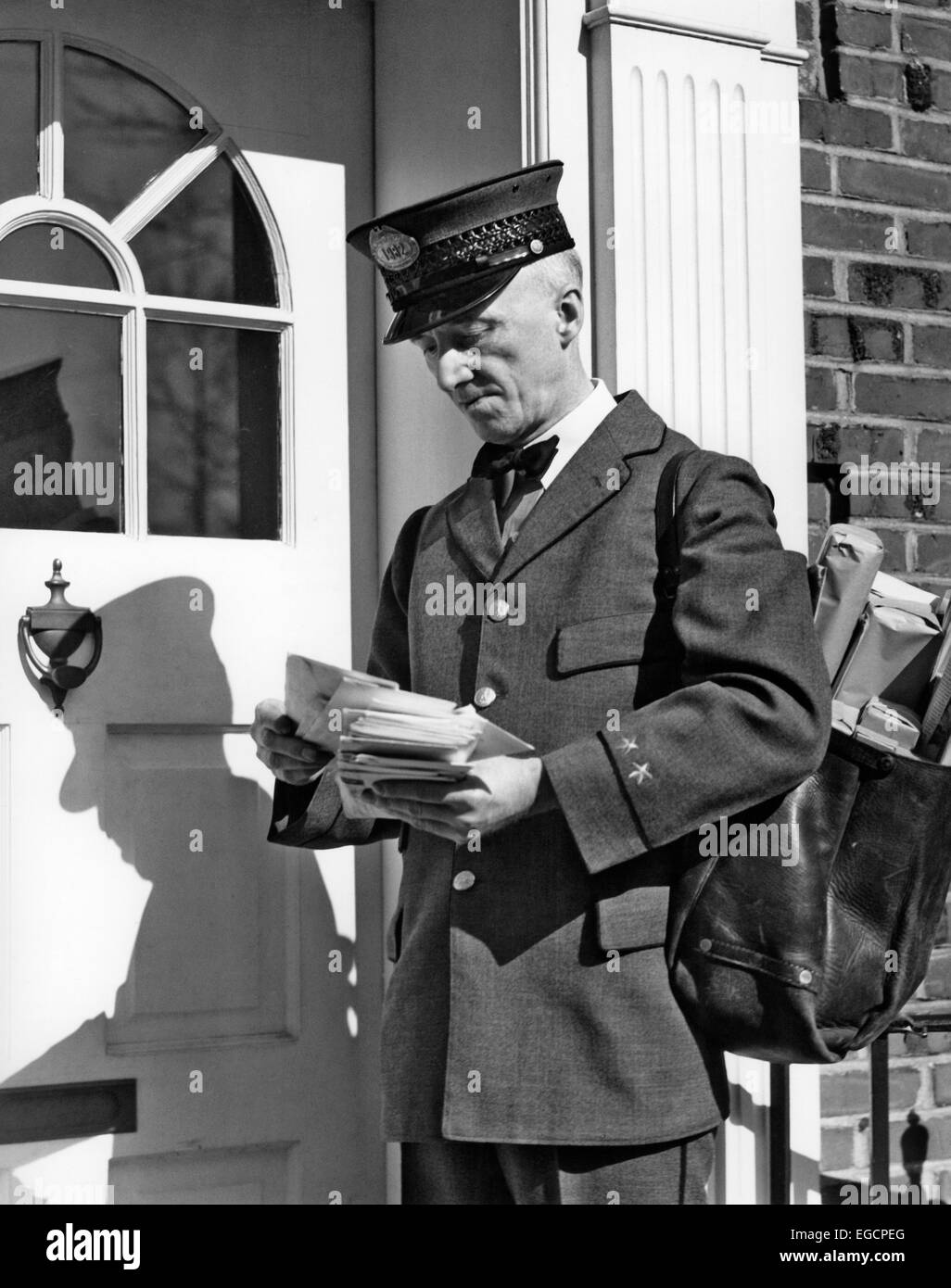 1930s 1940s POSTAL SERVICE UNIFORMED MAILMAN DELIVERING MAIL STANDING ON DOORSTEP SORTING LETTERS Stock Photo