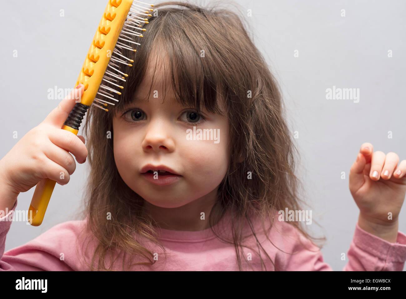 2year old girl brushing her hair stock photo 79233754