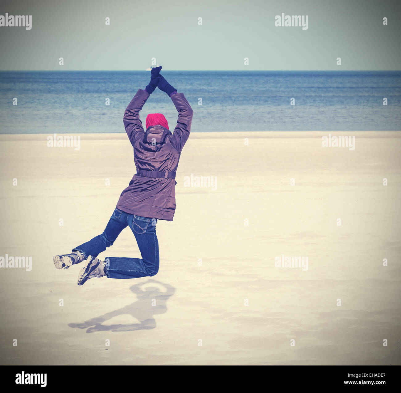 Retro filtered photo of woman jumping on beach, winter active lifestyle concept, space for text. Stock Foto