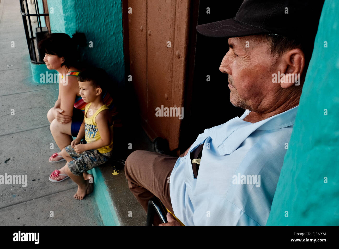 A man watches over his family on the doorstep to their home in the 500 year old city of Sancti Spiritus, Cuba. Cubans Stock Foto
