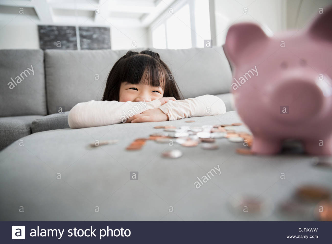 Smiling girl with piggy bank and coins Stock Foto