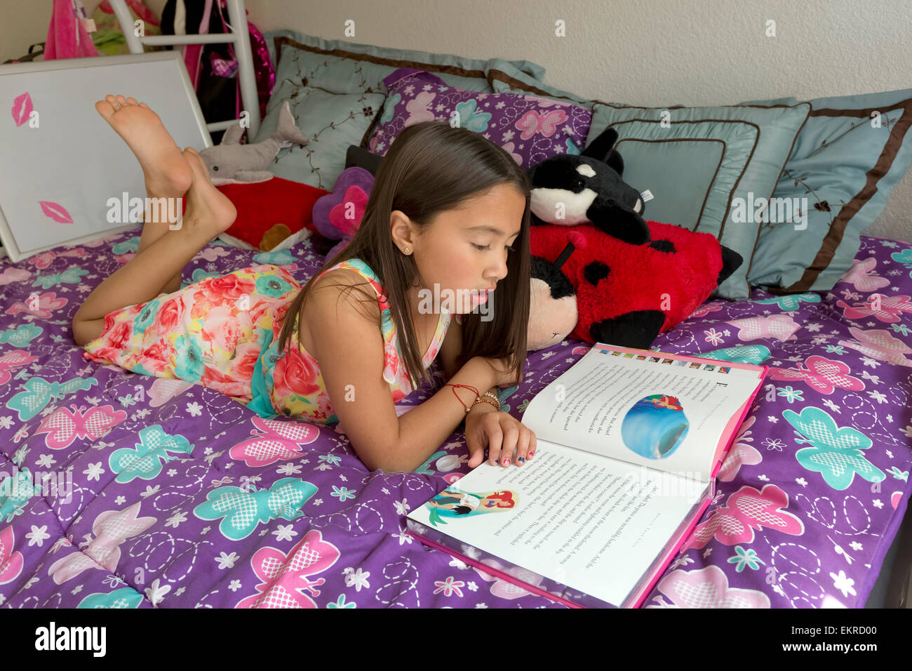 8 year old girl reading a story on her bed at home stock photo royalty free image 81035024 alamy. Black Bedroom Furniture Sets. Home Design Ideas