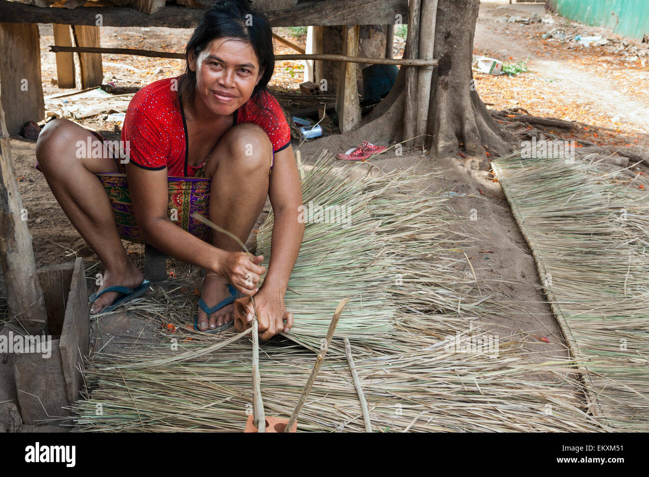 Cambodian Woman Weaving Palm Fronds To Make A House Roof