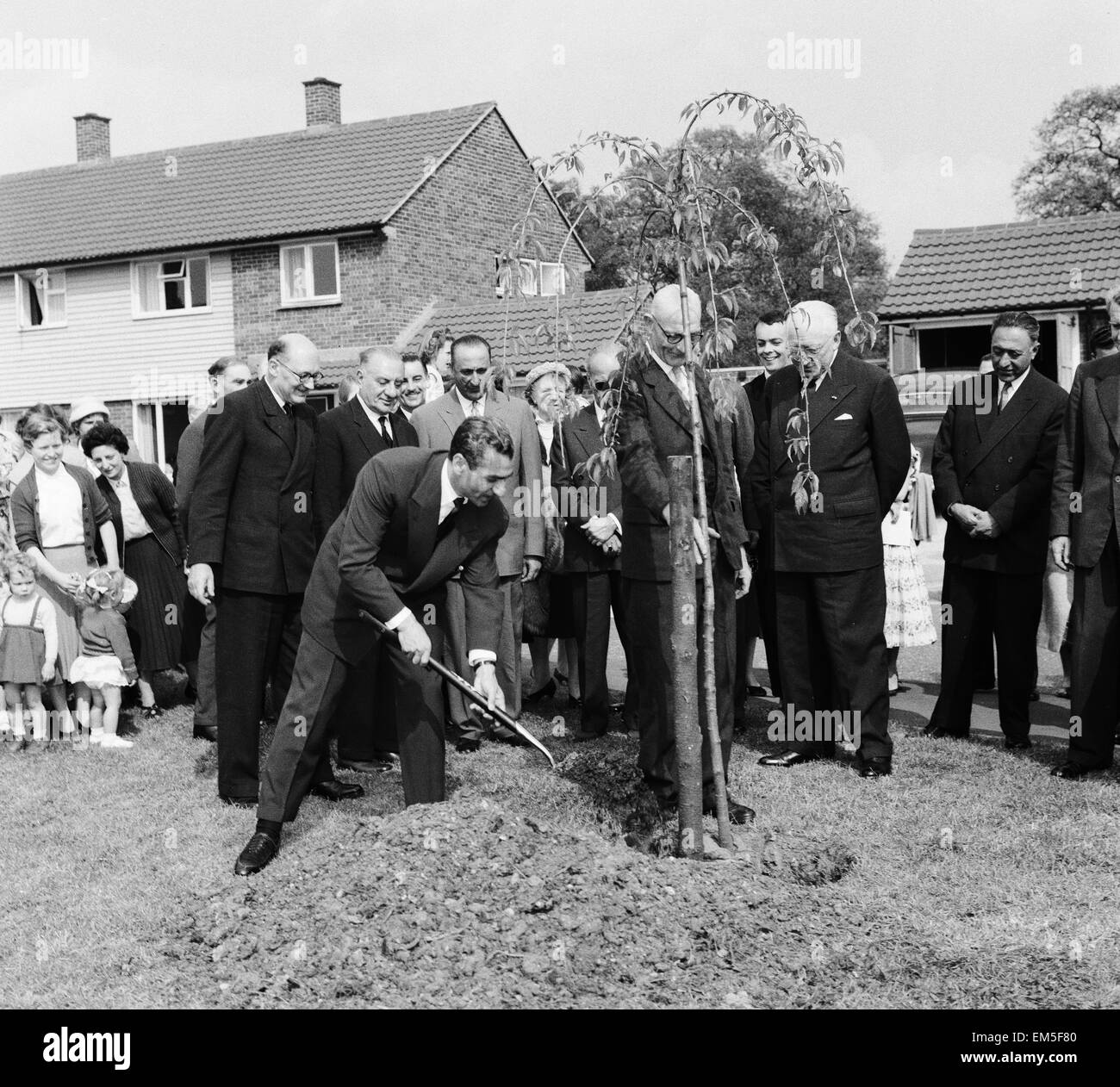 Mohammad-Reza Shah Pahlavi, the Shah of Iran plants a tree watched by residents of Makepieace Road in the new town Stock Photo