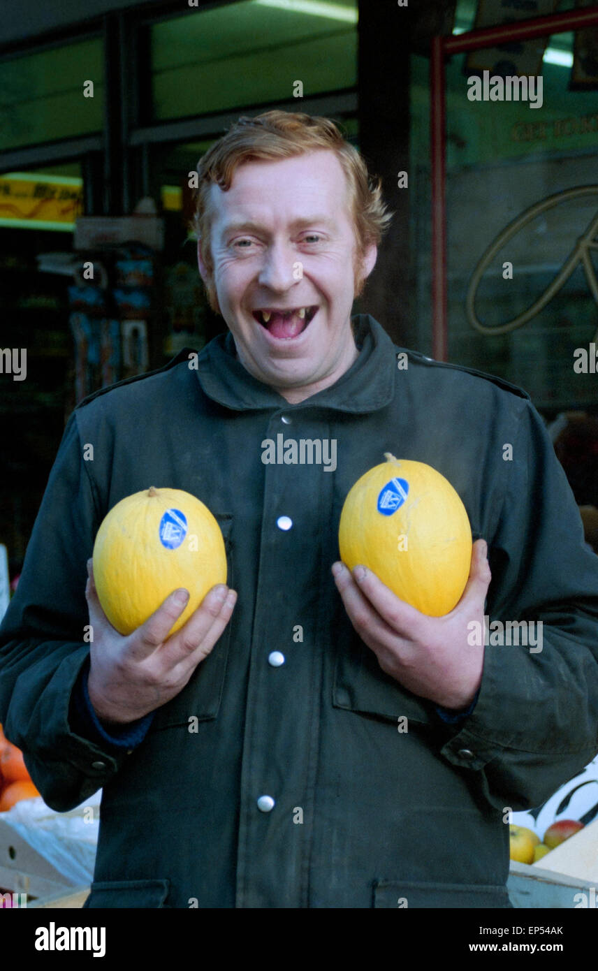 a smiling toothless greengrocer holding two grapefruit outside of his shop in southsea england in the 1990s Stock Photo