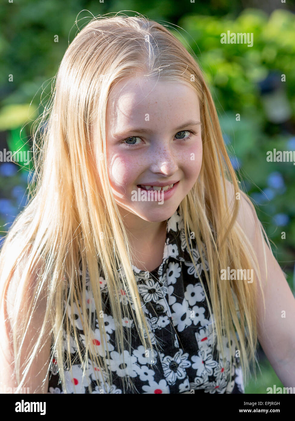 Blonde 8 Year Old Girl Sitting In A Garden Posing For The