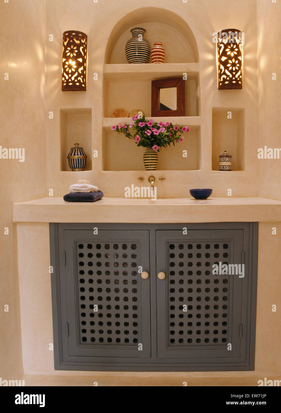Moroccan Bathroom Wall Lights : Wall lights on either side of alcove shelves above cupboard with blue Stock Photo, Royalty Free ...
