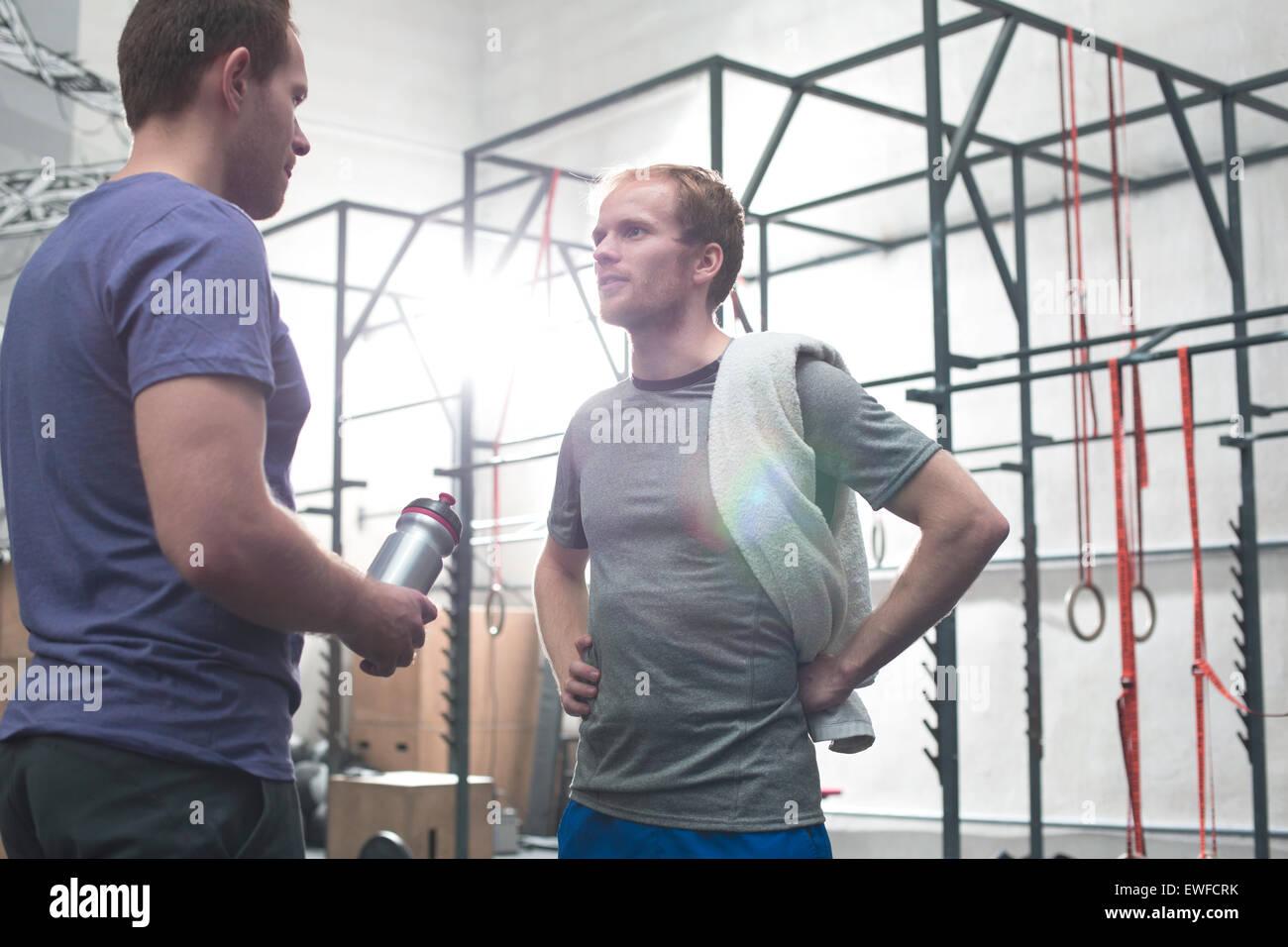 Male friends talking in crossfit gym Stock Photo