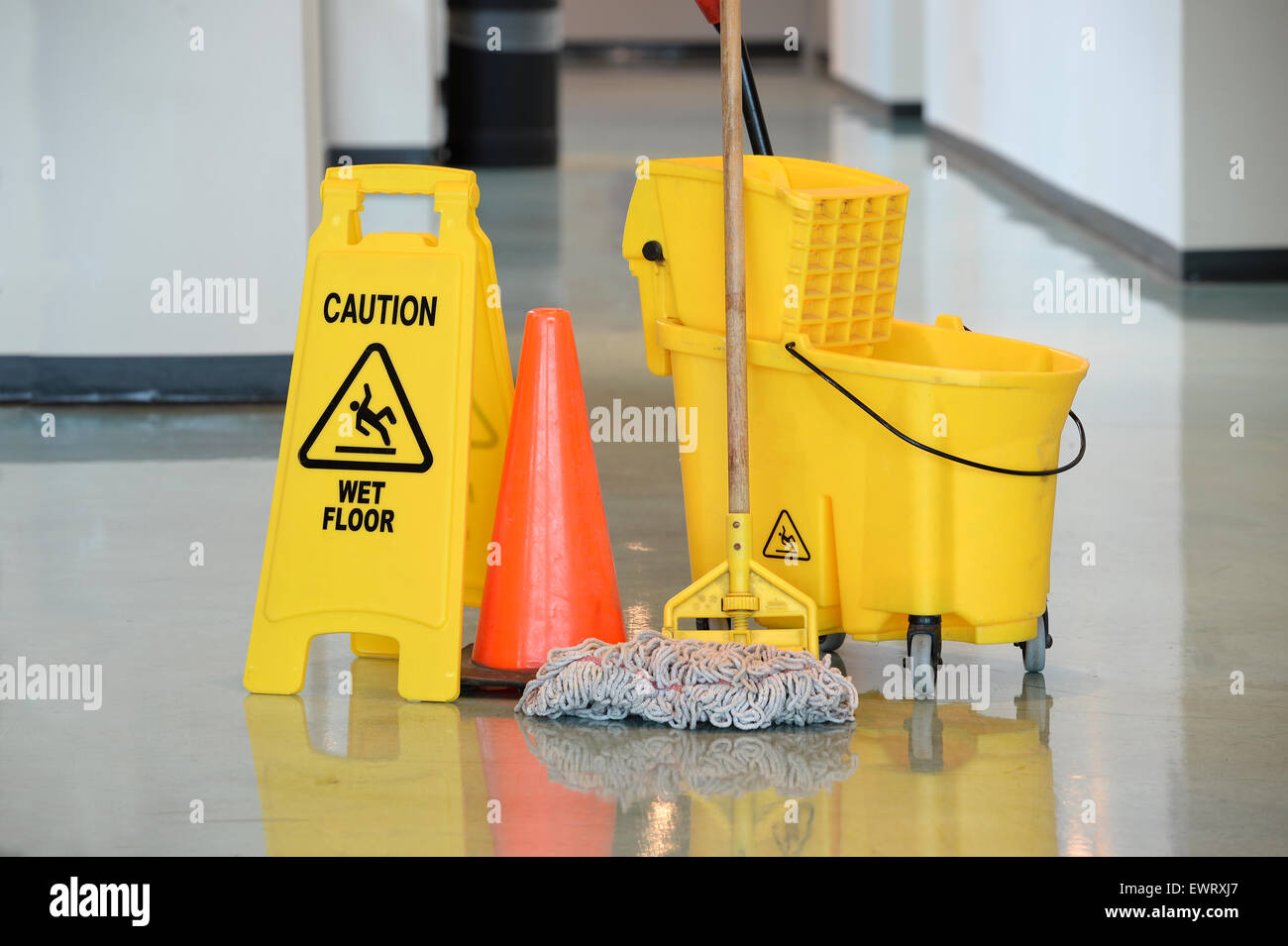 Caution Sign With Mop And Bucket On Office Floor Stock
