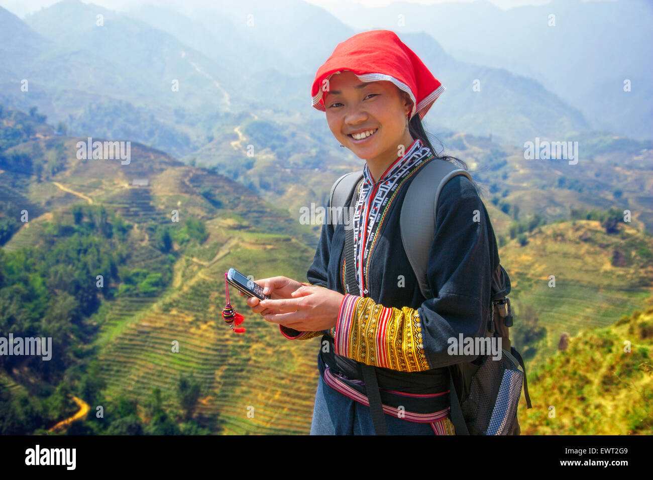 Stock Photo - Hmong girl tour guide on her cell phone in Sapa, Vietnam above rice paddy
