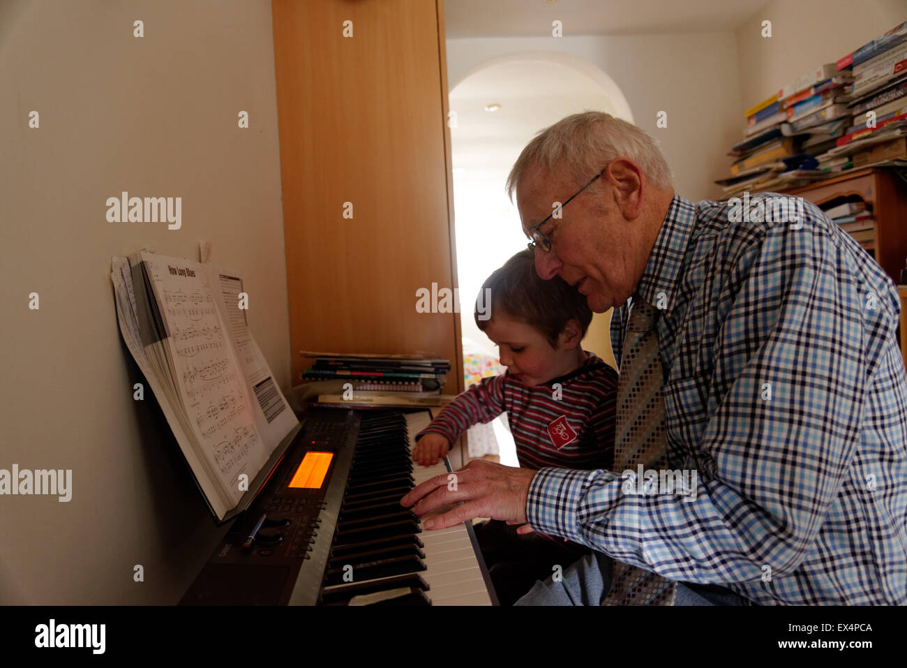 a-young-boy-3-yrs-old-playing-the-piano-with-his-grandfather-EX4PCA.jpg