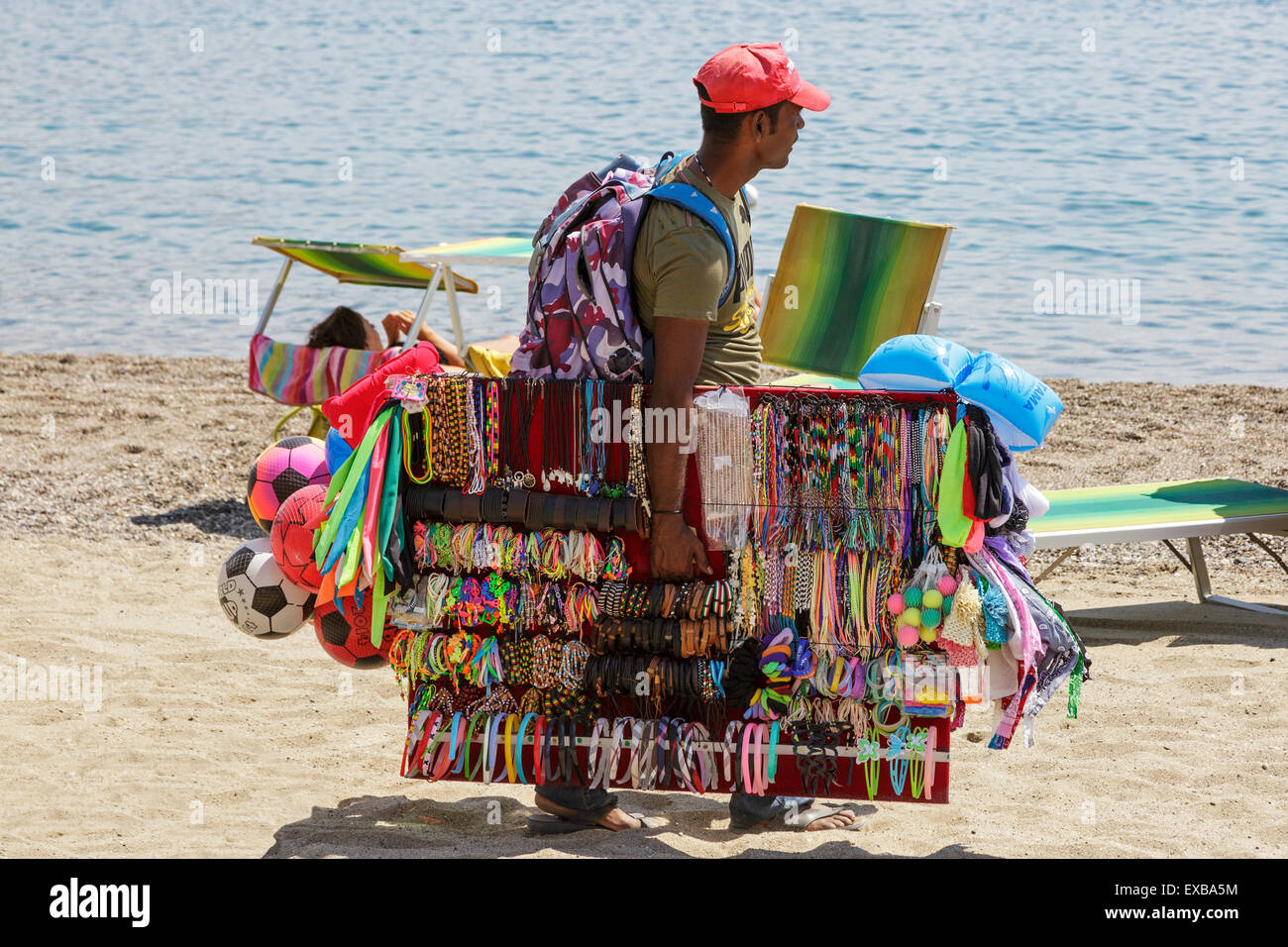 Man selling jewellery and toys on the beach at Giardini ...