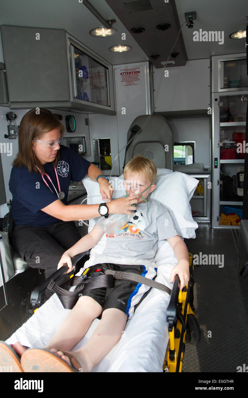 Female paramedic assisting young male patient in back of ambulance. Stock Photo