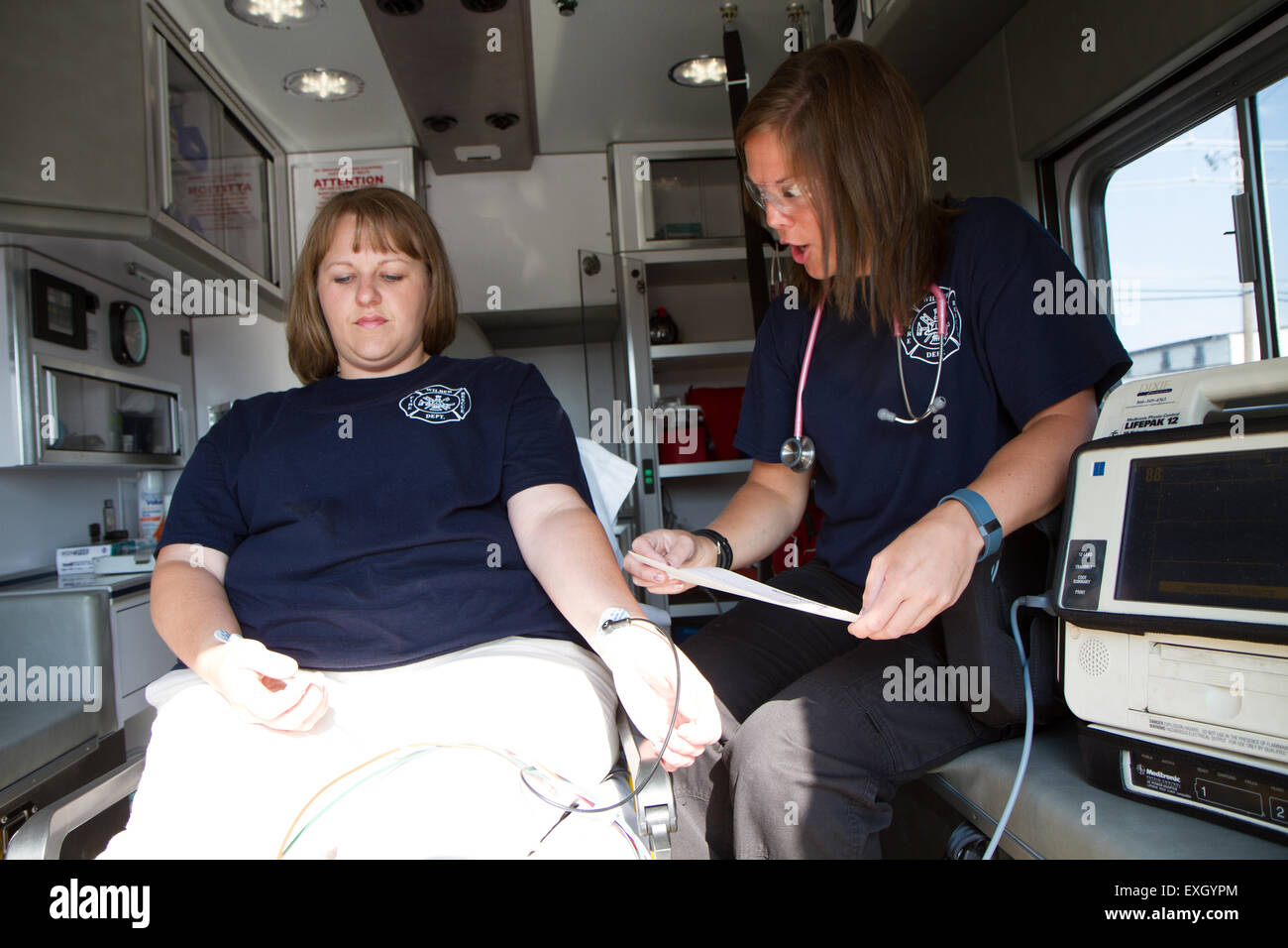 Female paramedics working in the back of an ambulance. Rural volunteer US fire department. Stock Photo