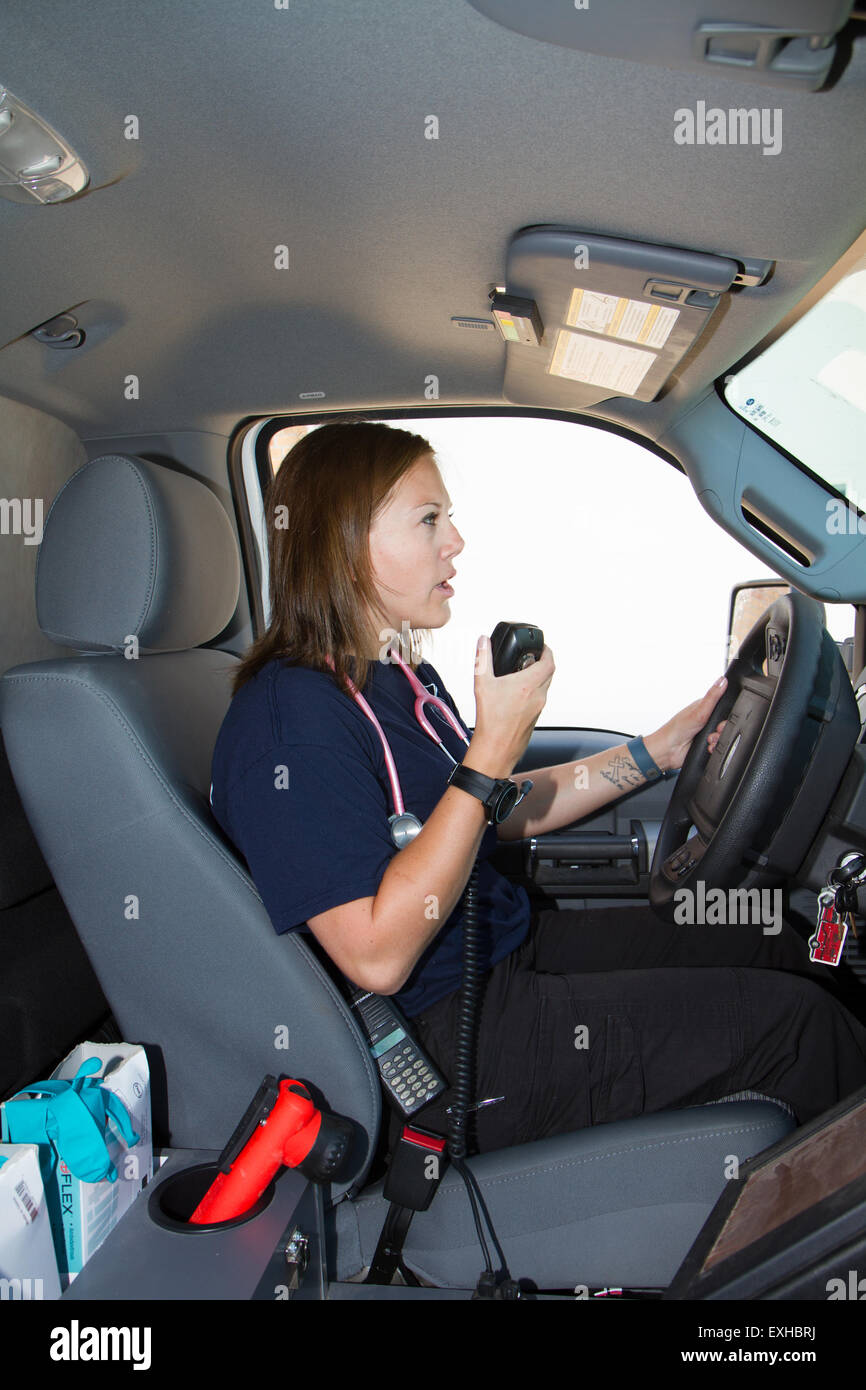 Female paramedic EMT using radio in ambulance. Rural volunteer fire department ambulance. Stock Photo
