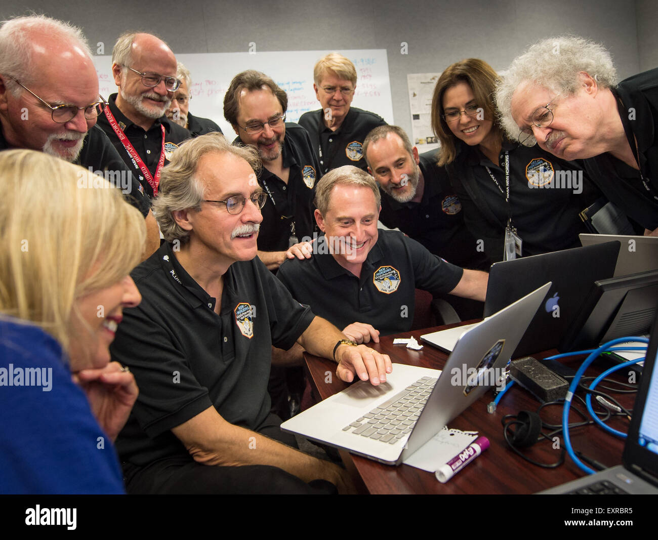 Members of the New Horizons team gather around a laptop and smile as they review new processed images from the New Stock Photo