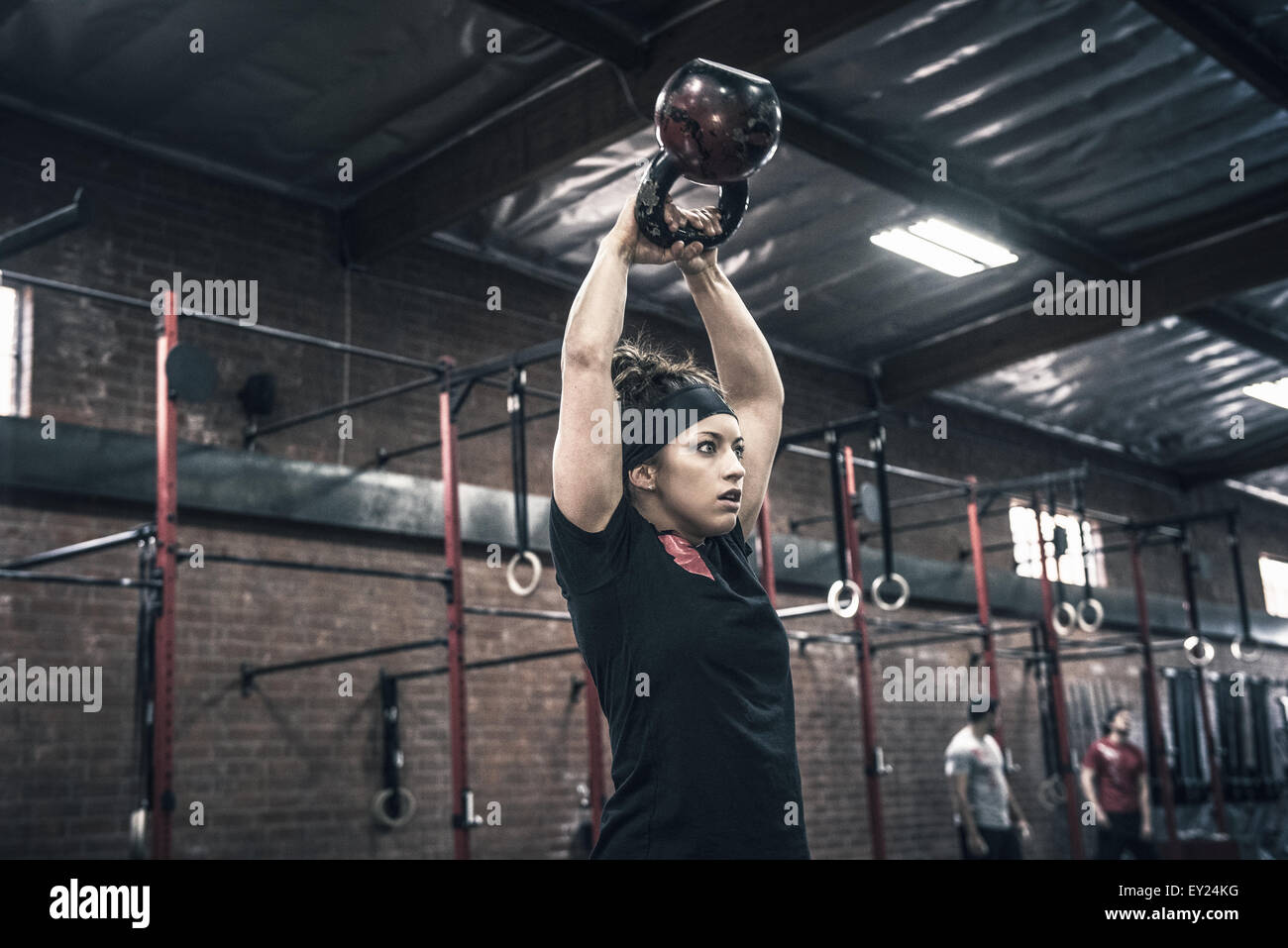 Young woman holding up kettle bells in gym Stock Foto