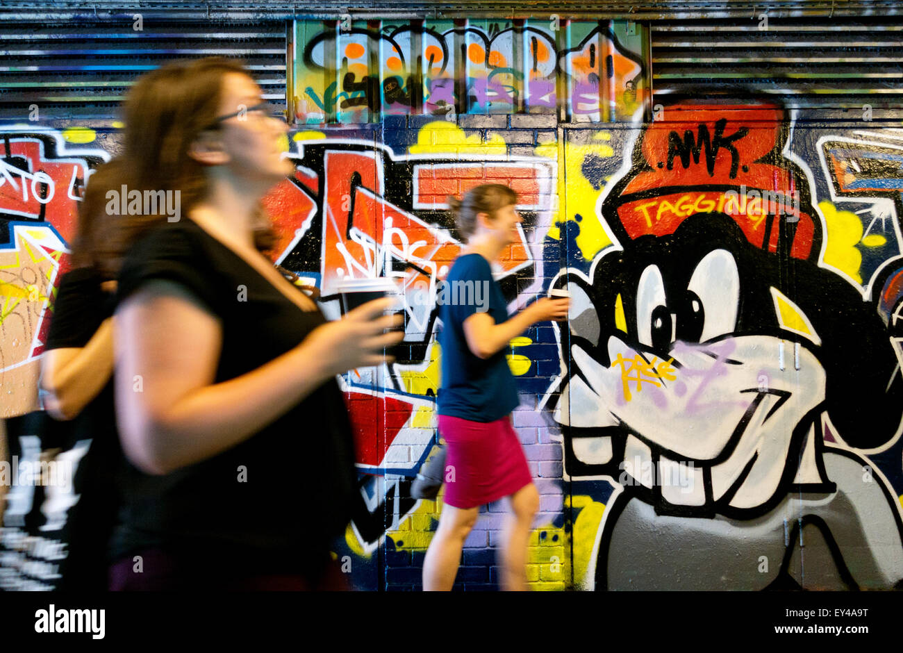 people-walking-past-the-graffiti-on-the-