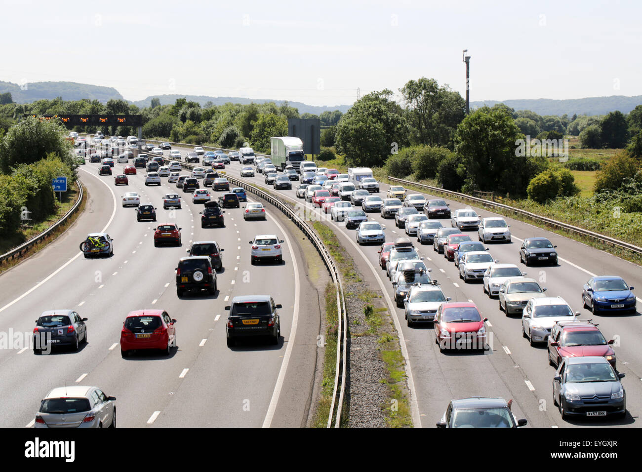 Queues of heavy traffic, in both directions, on the motorway during a busy summer weekend. Stock Photo