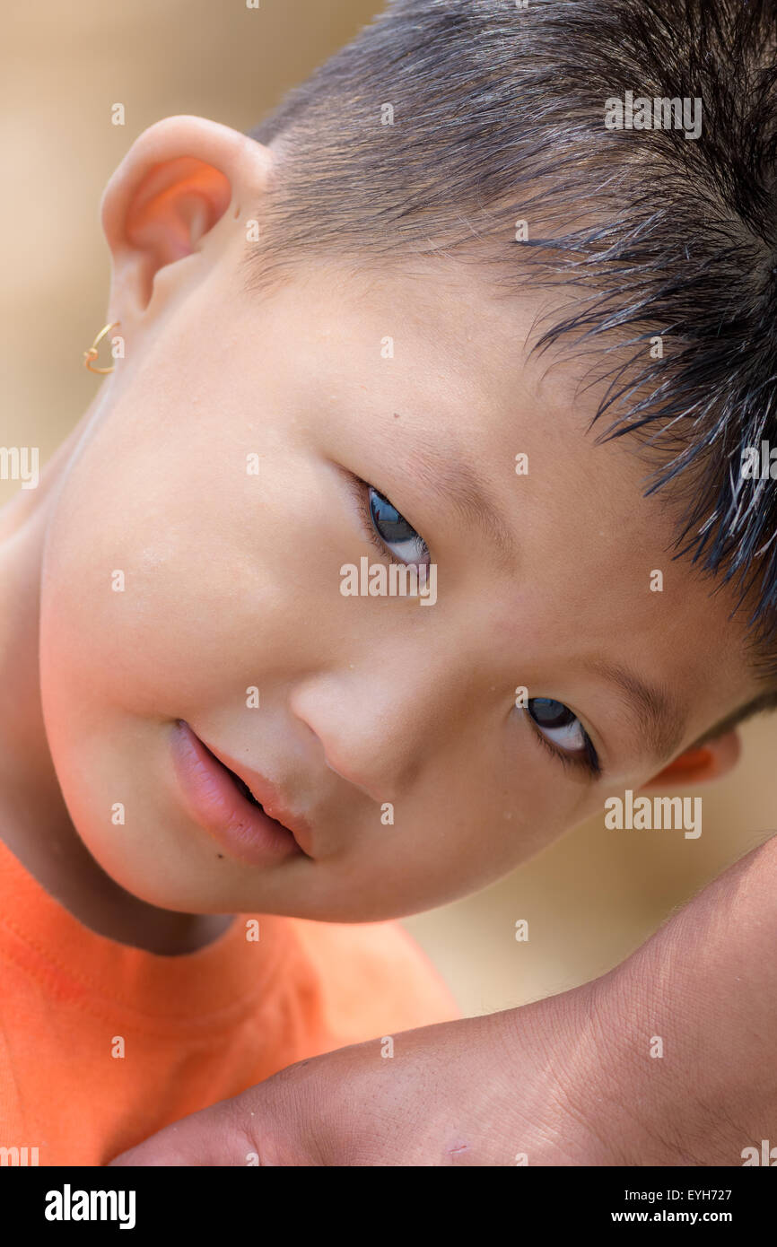 Portrait of a little mongoloid boy happy and innocent with copy space, curious look in the eyes Stock Photo