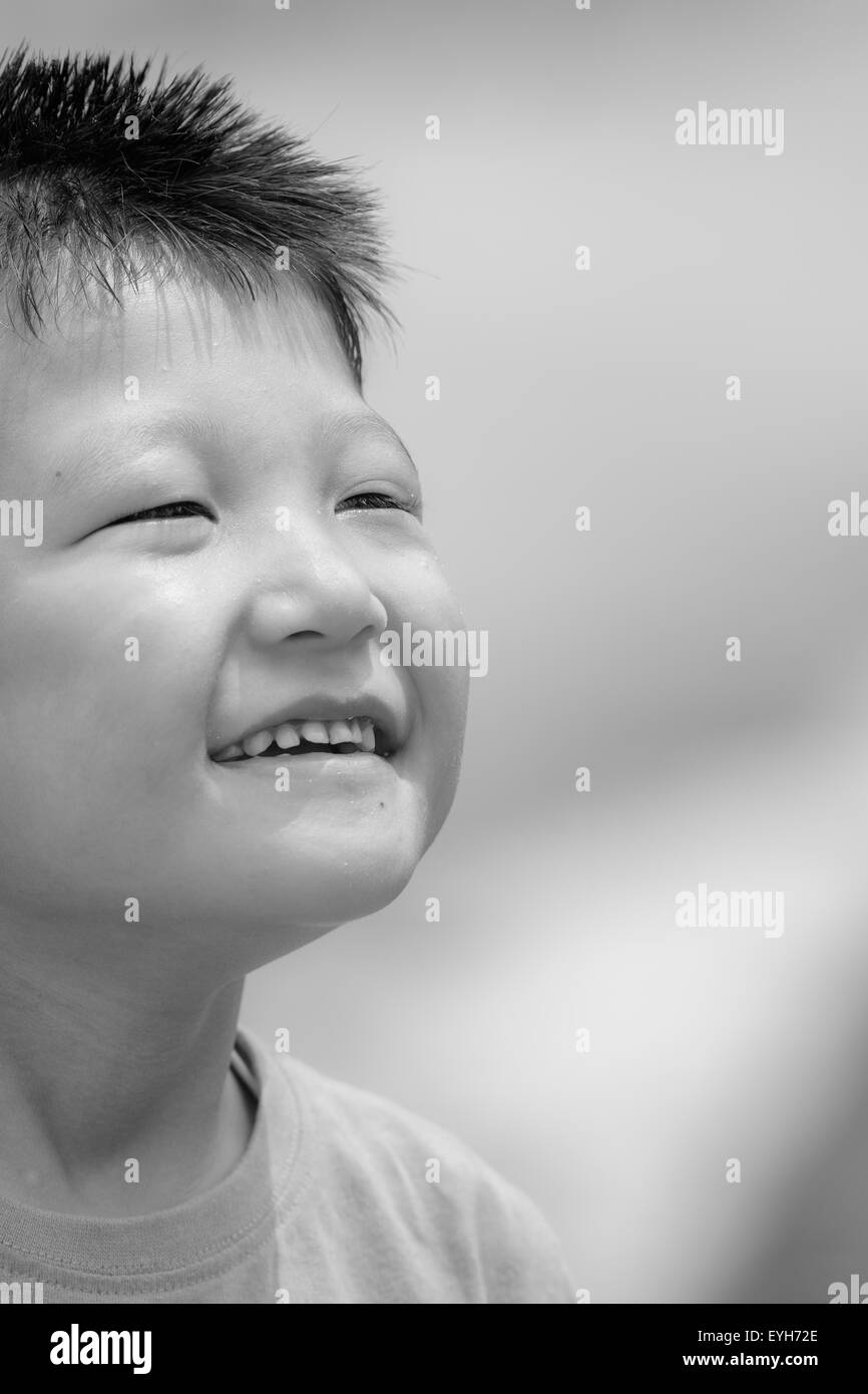 Black and white Portrait of a little mongoloid boy happy and smiling with copy space Stock Photo