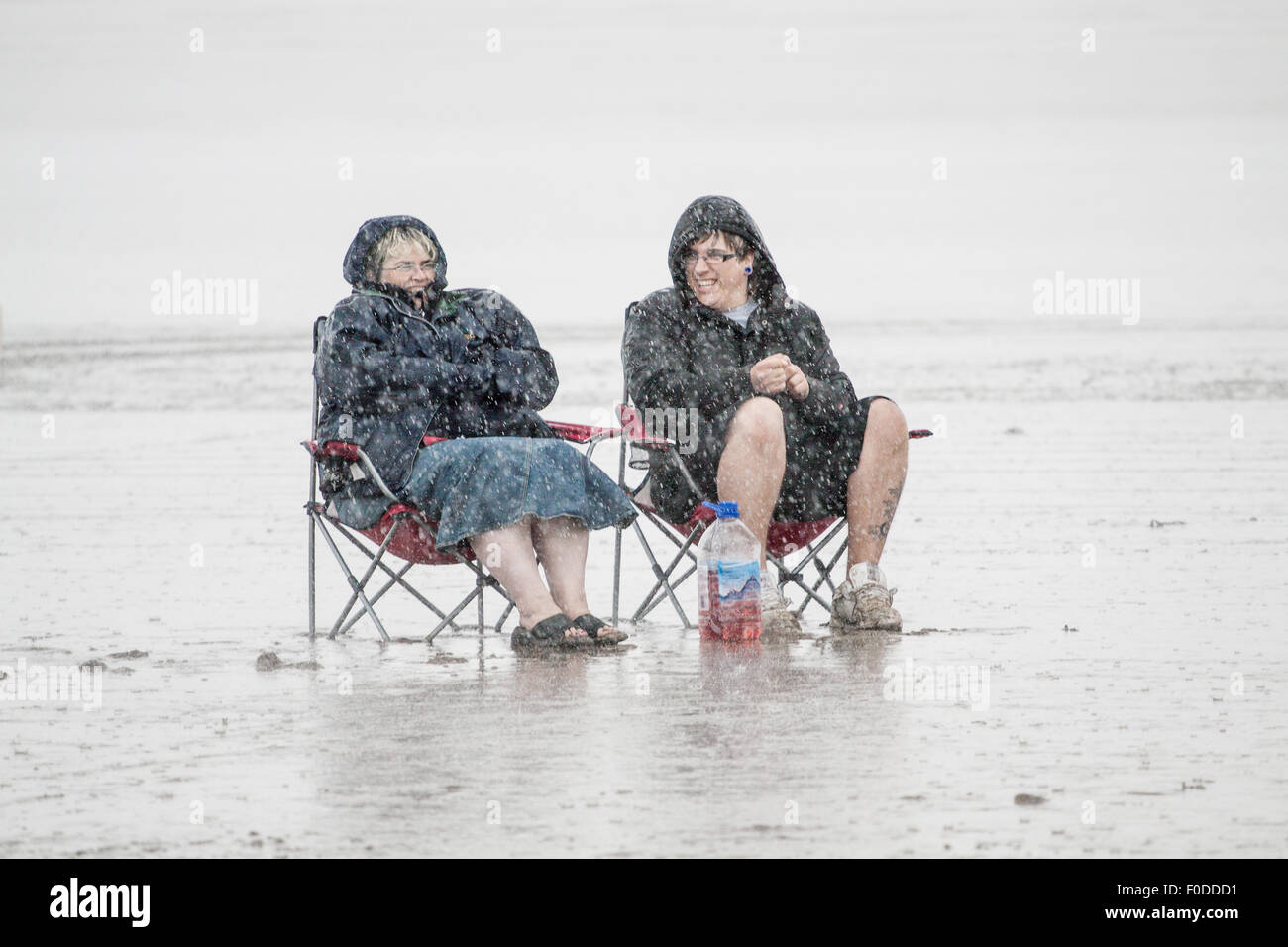 two-people-sitting-on-a-beach-in-a-rains