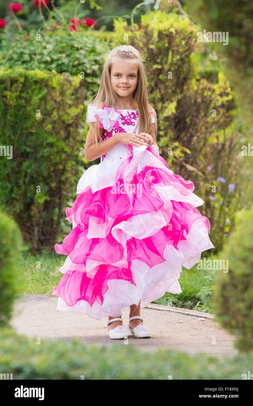 Happy six year old girl in a lush evening pink dress for Gardening tools for 6 year old
