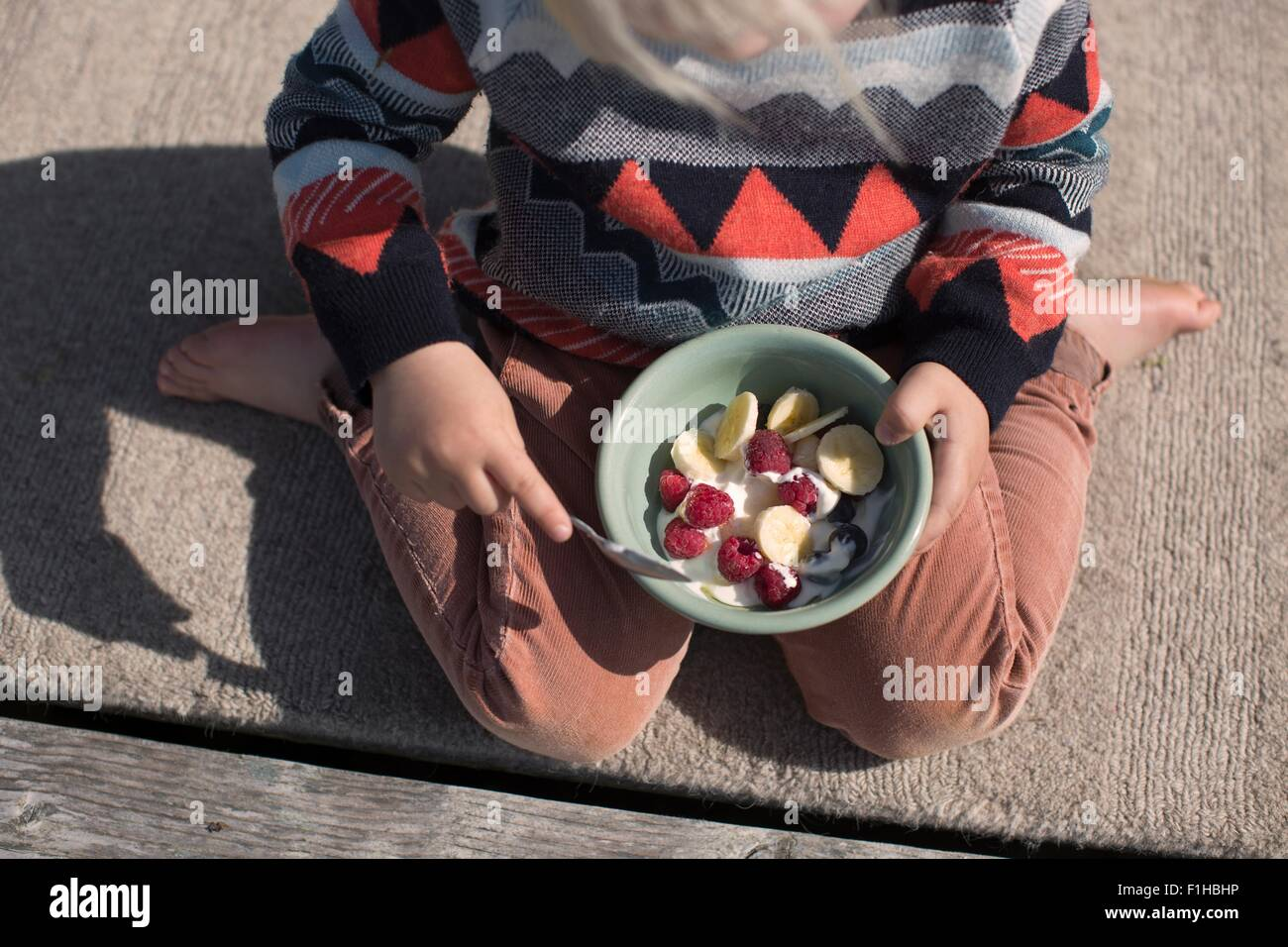 Boy holding bowl of fruit, high angle Stock Foto