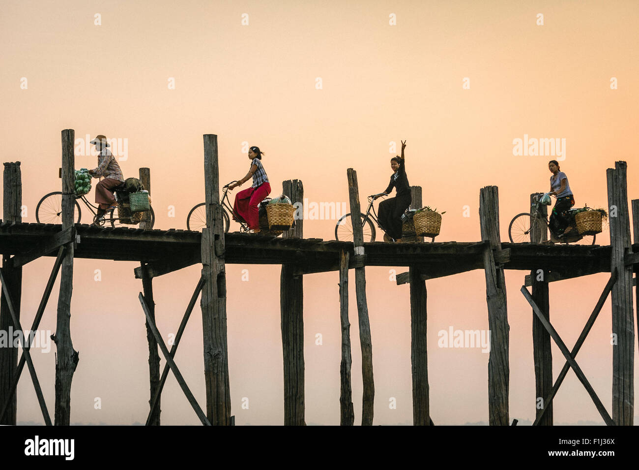 Burmese woman flashes peace sign on a bike riding over U Bein Bridge at sunset.  U Bein Bridge Burma, Myanmar Stock Foto