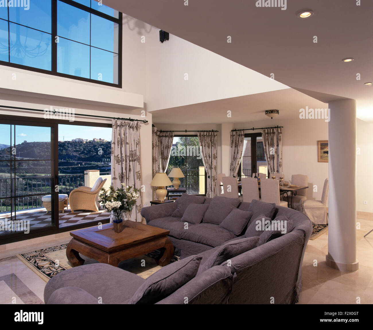 Grey l shaped sofa in modern double height spanish living for Double height living room designs