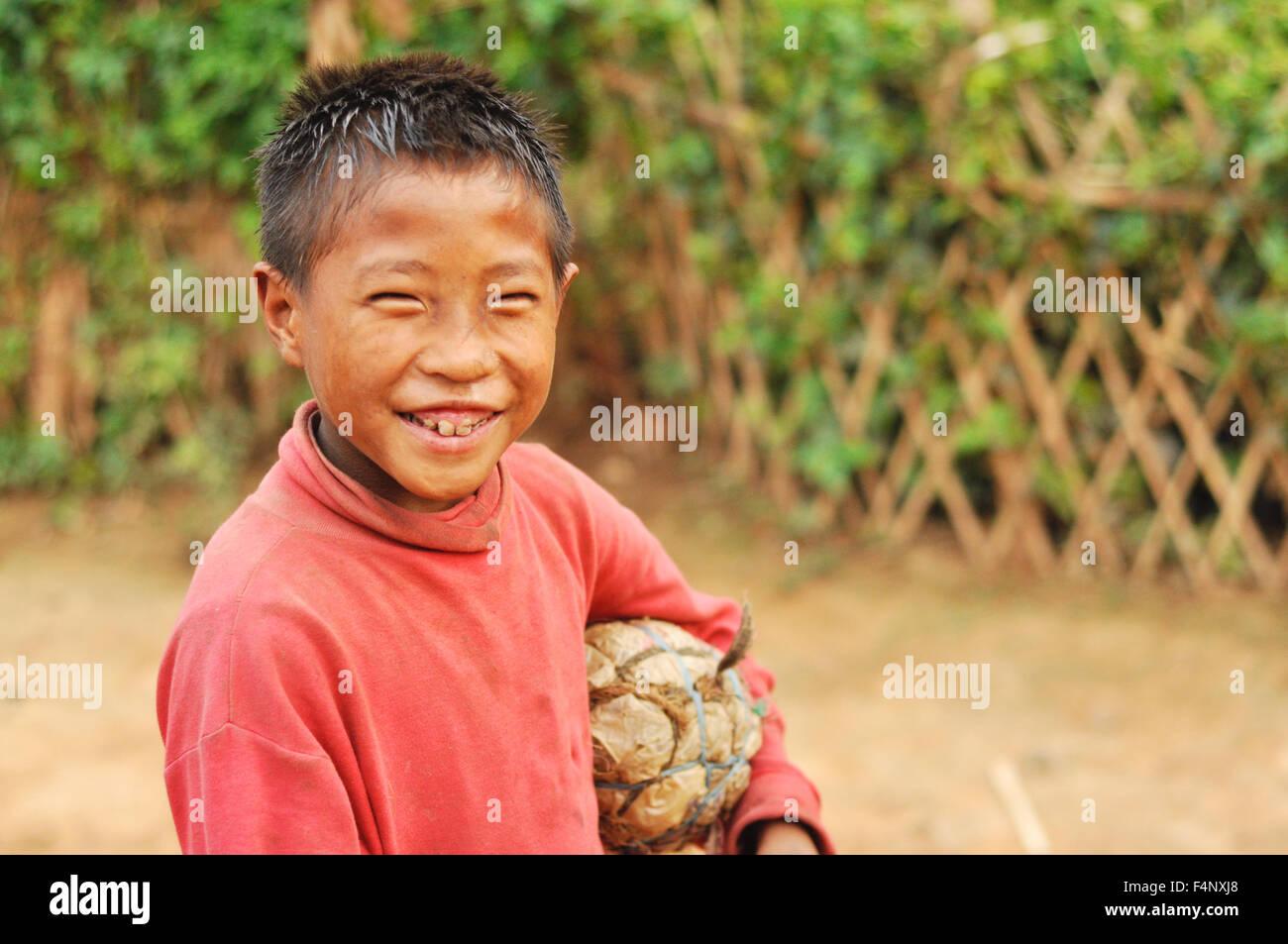 Nagaland, India - March 2012: Happy young footballer with self-made ball smiles at camera, Nagaland, remote region Stock Photo
