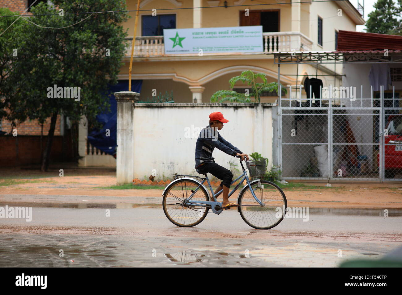 asian-boy-on-bicycle-in-rain-F540TP.jpg