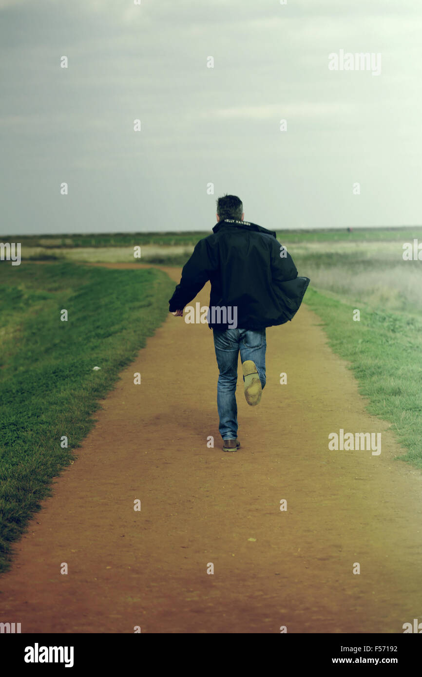 Middle aged man running in rural coastal area Stock Foto