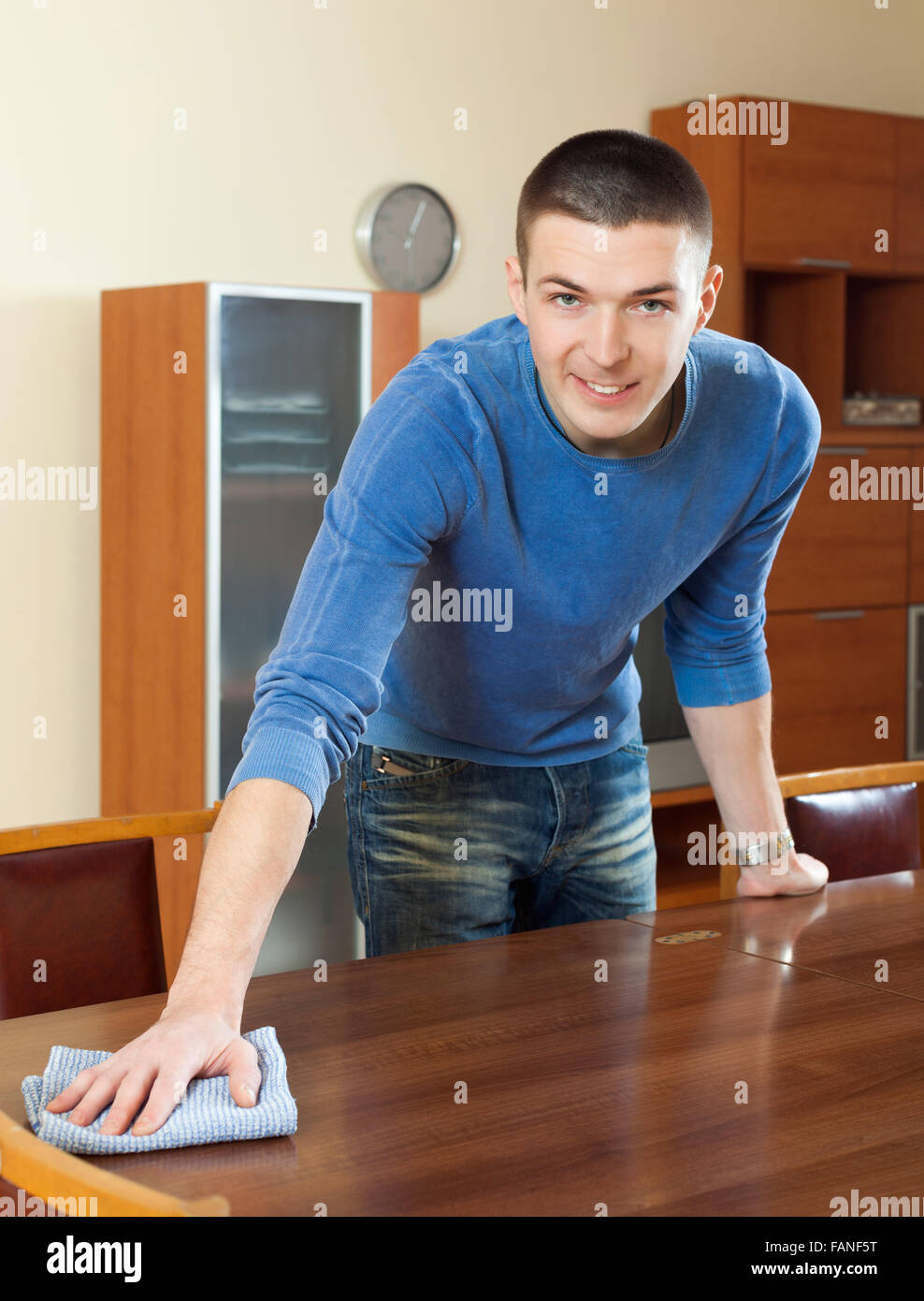 Happy Man Polishing Table With Furniture Polish At Home
