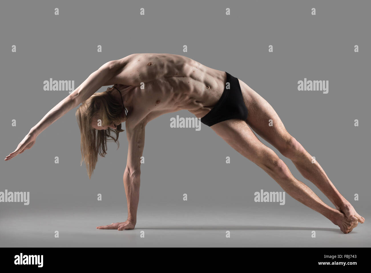 Sporty muscular young yogi man doing variation of Side ...