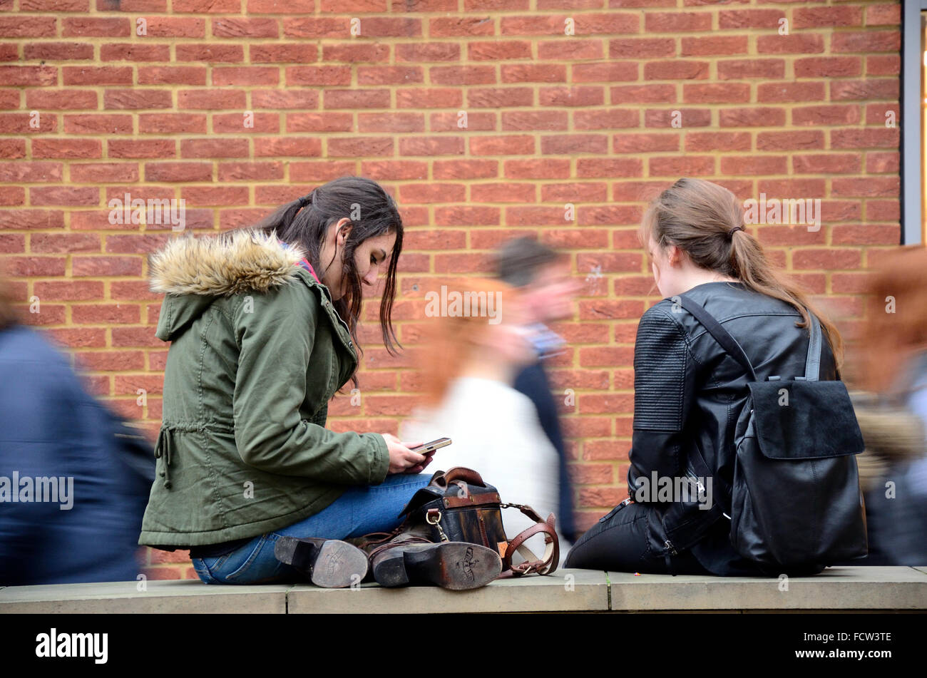 two-teenage-girls-sat-on-a-wall-together